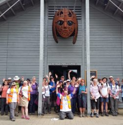 A large group of walkers cheering outside the exhibit hall at Sutton Hoo with Raedwald's rust-orange mask looking down on them