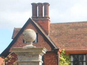 Roof and chimney of an old red brick Hall