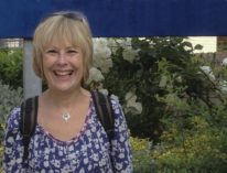 Image of Leslie Dolphin in a blue and white floral top. She is smiling and standing in front of a large white rose bush and a blue sign