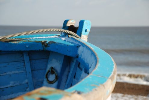 Blue and white wooden dinghy on the beach
