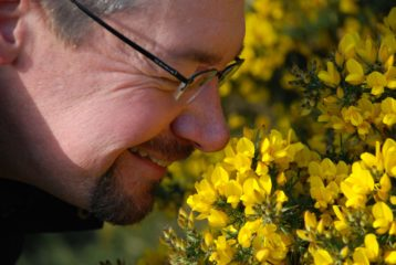 David Falk (Festival Director) smiling and sniffing bright yellow gorse flowers