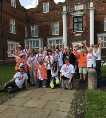 A group of walkers gathered outside the front of Christchurch Mansion (large red brick building with white windows and white pillars), cheering because they just finished their Challenge Walk!