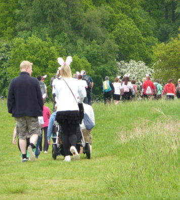 A long line of walkers walking along a track through a grassy field. Some are pushing buggies and wearing bunny ears!