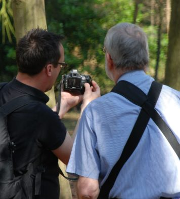 A view of two men from behind, one is showing the other something on the back of their digital camera