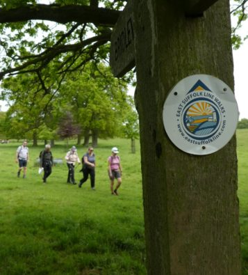 A line of walkers walking through a green field in the background, with a waymarker disc for the East Suffolk Lines Walk attached the a wooden post in the foreground