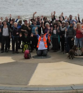 A large group of walkers gathered on a giant compass at Ness Point in Lowestoft. The sea behind them is rather grey and choppy!