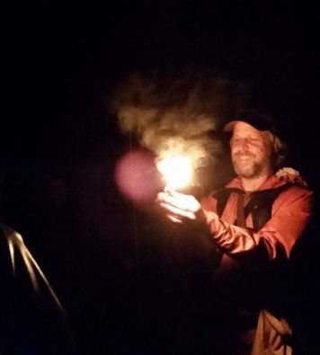 A picture of a man smiling while he creates flames in the dark