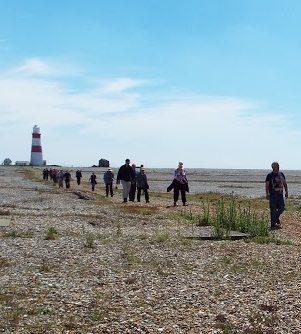 Walkers on a stony beach on a sunny day